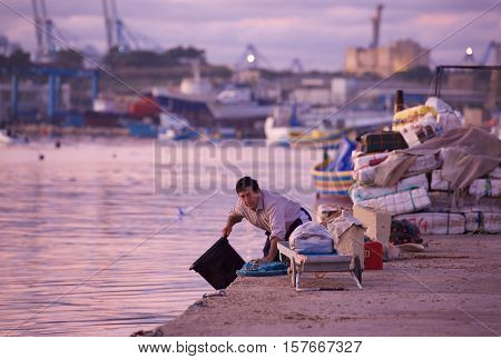 MARSAXLOKK, MALTA-NOV 23: fisherman preparing for fishing in typical colorful maltese background in violet sunset on Nov 23, 2014. Daily life of maltese people in Marsaxlokk, Malta. Working fisherman