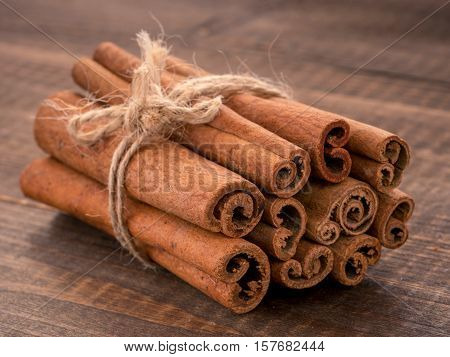 Ground cinnamon, cinnamon sticks, tied with jute rope on wooden background. Close up