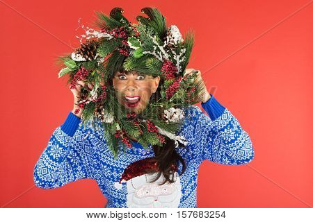 Woman Looking Through Christmas Wreath