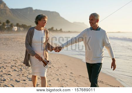 Loving Mature Couple Strolling On The Beach.