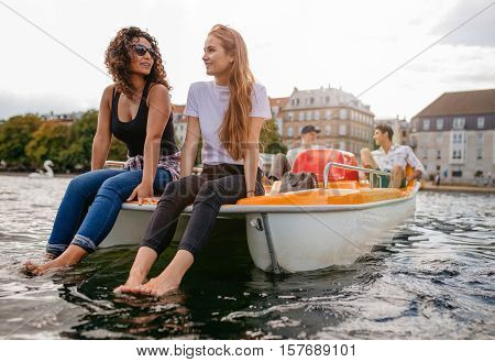 Shot of two women sitting in front pedal boat with feet in water and man in background. Teenage friends enjoying boating in the lake.
