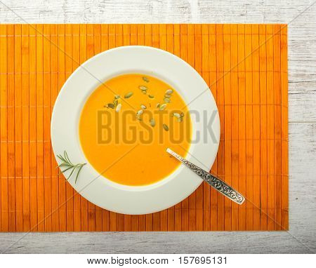 pumpkin cream soup with pumpkin seeds in a white plate with a spoon on a orange napkin closeup