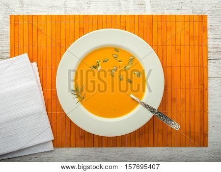 pumpkin cream soup with pumpkin seeds in a white plate with a spoon on a orange napkin top view
