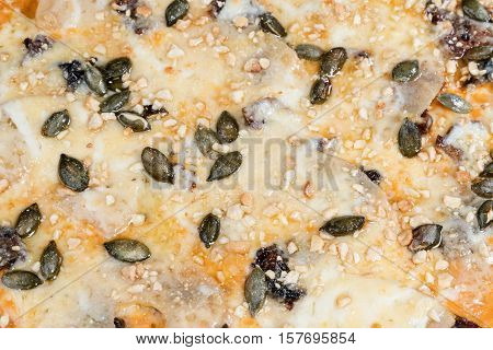 Sweet pizza with pineapple dried pears and pumpkin seeds close-up