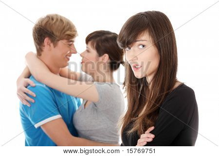 Sad brunette girl jealousy about her friend. Isolated on white background.