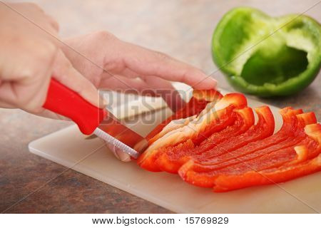 Female chopping food ingredients (paprika) on the kitchen.