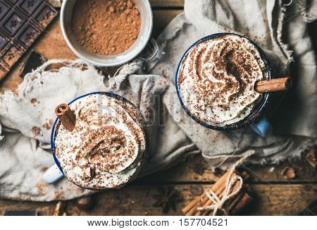 Close-up of hot chocolate with whipped cream and cinnamon sticks served with anise, nuts and cocoa powder on rustic wooden background, top view, selective focus, horizontal composition