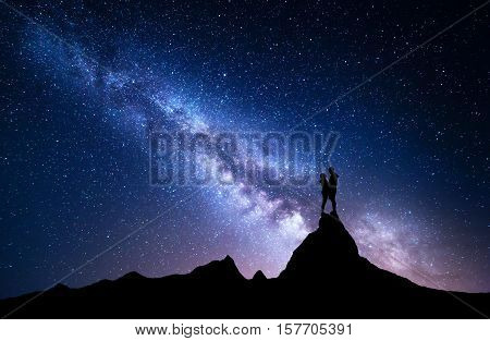 Milky Way with silhouette of people. Night landscape with starry sky. Standing man and woman on the top of mountain. Hugging couple against milky way. Beautiful galaxy. Universe. Travel. Bright stars