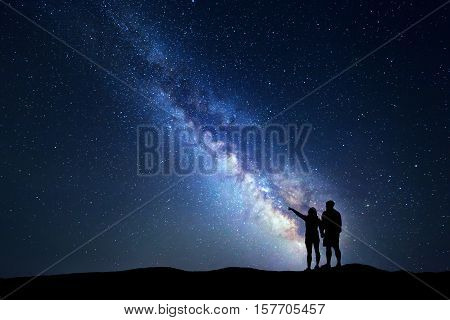 Milky Way with people on the mountain. Landscape with night sky with stars and silhouette of standing happy man and woman who pointing finger in starry sky. Blue Milky way. Galaxy. Bright stars