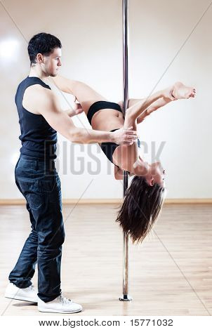 Pole dance trainer. Young man training woman.