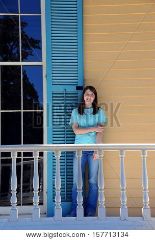 Woman visitor poses besides tall window on front porch of Lakeport Plantation on the Mississippi Delta. She is wearing jeans and a turquoise tee shirt.