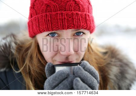 Girl drinking hot tea in the winter forest portrait. A young girl in warm winter clothes holding a cup with a drink on the background of the winter forest,portrait. Christmas girl outdoor portrait.
