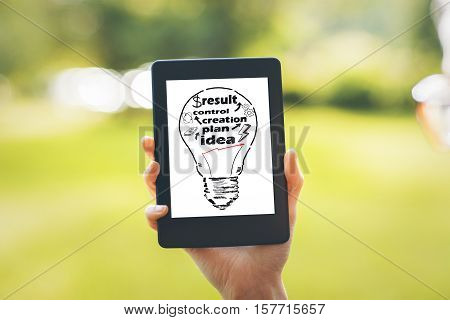 Hand holding tablet with lamp sketch on green background. Business process concept