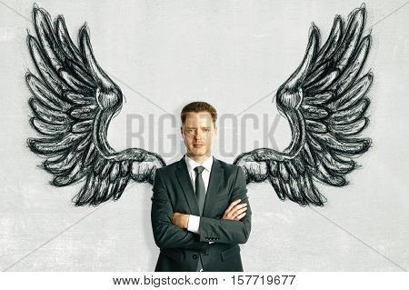 Confident businessman with drawn wings on light background. Freedom concept
