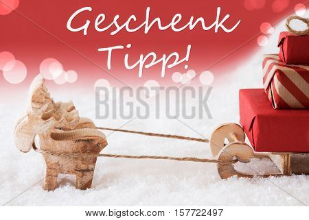 German Text Geschenk Tipp Means Gift Tip. Moose Is Drawing A Sled With Red Gifts Or Presents In Snow. Christmas Card For Seasons Greetings. Red Christmassy Background With Bokeh Effect.