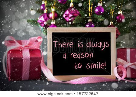 Christmas Tree With Rose Quartz Balls, Snowflakes And Bokeh Effect. Gifts Or Presents In The Front Of Cement Background. Chalkboard With English Quote There Is Always A Reason To Smile