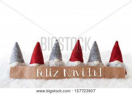 Label With Spanish Text Feliz Navidad Means Merry Christmas. Christmas Greeting Card With Gnomes. Isolated White Background With Snow.