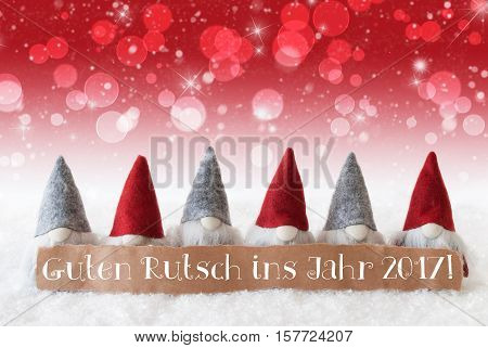 Label With German Text Guten Rutsch Ins Jahr 2017 Means Happy New Year 2017. Christmas Greeting Card With Red Gnomes. Sparkling Bokeh And Christmassy Background With Snow And Stars.