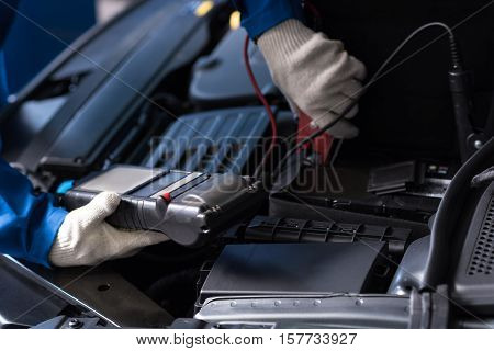 Look it correctly. Close up of special device in hands of professional mechanic checking car engine while conducting car meintenance
