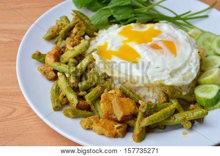spicy stir fried yard long bean with fat pork curry and creamy egg yolk on rice