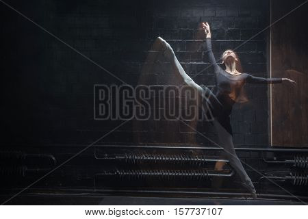 Amazing twine . Involved talented young gymnast jumping in the twine while raising her hands and being in motion