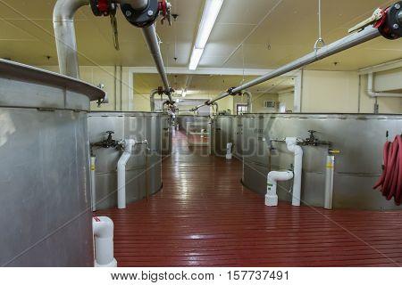 Inside modern fermentation room with large metal vats in bourbon distillery.