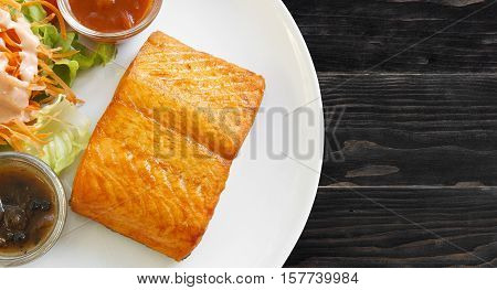salmon steak with black pepper sauce tomato sauce and vegetable salad in white dish on the top view black or dark wood table with copy space isolated on white included clipping path