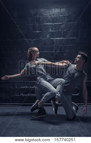 Dancing atmosphere . Involved concentrated young dancer sitting on the leg of other athlete while performing together in the dark lighted room and expressing concentration and confidence