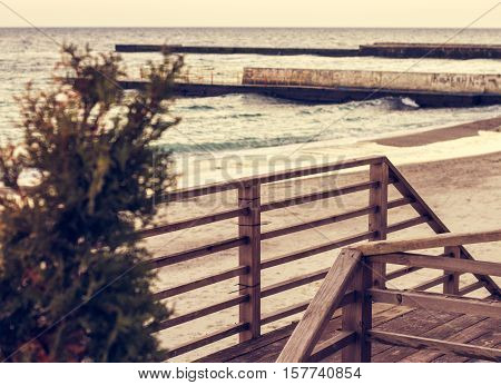 wooden ladder with railings on the beach during warm sunset