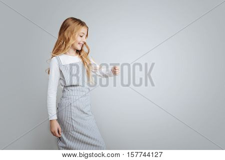 Upbeat mood. Positive gelighted cute little girl smiling and cooking her dish in the on the cooker while standing isolated on grey background