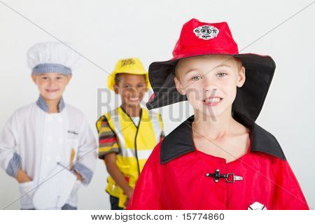 little boy as firefighter, background is kids as chef and construction worker