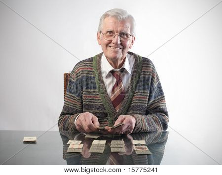 Smiling senior man playing cards