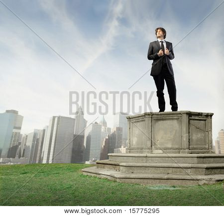 Bossy businessman on a pedestal with cityscape on the background