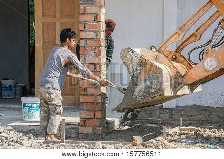 Labuan,Malaysia-April 7,2016:Construction site workers during concrete pouring into formwork at housing area at Labuan,Malaysia on 7th April 2016.