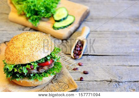 Sandwich with roasted bean cutlet, lettuce, red pepper and cucumber. Delicious sandwich on wooden background with blank space for text. Veggie breakfast sandwich recipe. Vintage style. Closeup