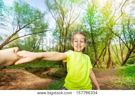 Portrait of smiling seven years old girl having fun in the forest