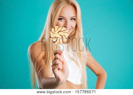 Portrait of a pretty charming woman with long hair showing lollipop isolated on the blue background. focus on lollipop