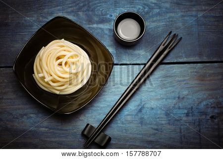 Spaghetti macaroni in black ceramic dish and chopsticks at wooden vintage table background with sake cup.