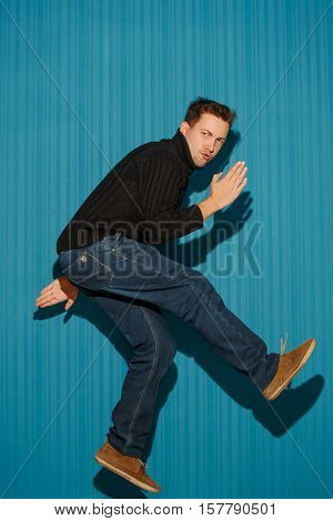 Portrait of young man with serious facial expression running over blue studio background