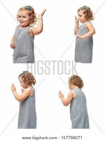 Young little girl with curly hair in gray dress standing and giving high five over isolated white background