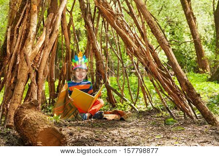 Happy boy in Red Indian's costume reading blanked book, sitting in wigwam in the forest