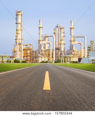 Oil refinery and asphalt road with sky background.