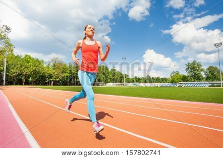 Portrait of active young woman running at the stadium's track and listening music in summer