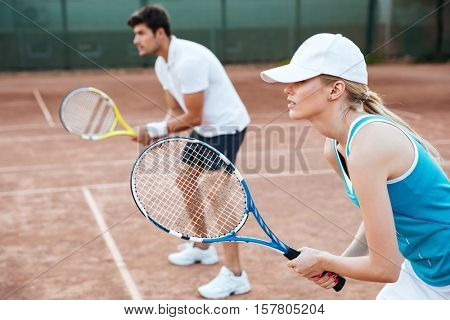 Side view of tennis woman and man on court