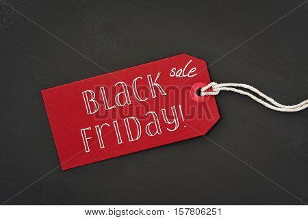 a red paper label with the text black friday sale written in it against a dark gray background