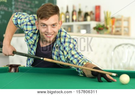 Young handsome man playing billiards in billiard club