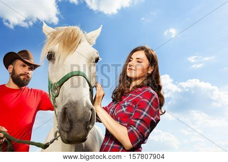 Portrait of young couple standing with their purebred white horse against the blue sky