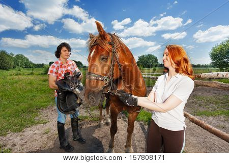 Young couple preparing for horseback ride, saddling their beautiful bay horse at the farm