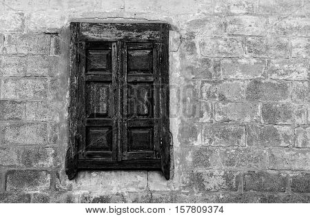 Old window with closed wooden shutter in an old Ukrainian country house.