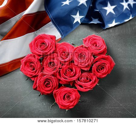 Heart shape of roses and USA flag on gray background. Symbol of America
